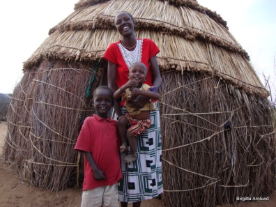 Catherine with two of her children in from of her hut